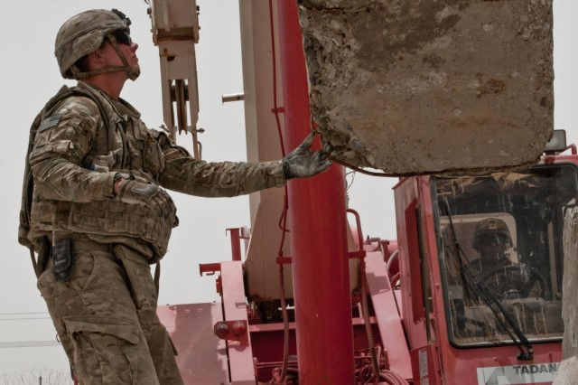 Pvt. Tyler Garlitz (left), a native of Dayton, Ohio, and Sgt. Juan Mendoza (driving), a native of Miami, both heavy equipment operators with the 687th Engineer Company, 46th Engineer Battalion, 1st Maneuver Enhancement Brigade, hoist one of the last concrete barriers at Forward Operating Base Walton, in Kandahar Province, Afghanistan, onto a trailer July 16, 2014. The FOB served as a strategic joint operating base with Afghan National Security Forces during Operation Enduring Freedom, and was officially closed the next day.