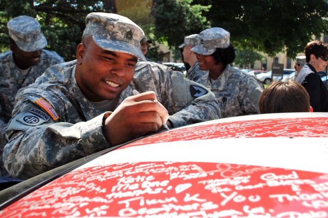 "Sgt. 1st Class Larry Howard Jr., U.S. Army Sustainment Command, adds his name to the thousands of autographs on the Wounded Warriors Family Support organization's 2014 Ford Mustang GT500 at Rock Island Arsenal, Ill., July 16. The Mustang is being driven to 65 cities in 48 states on a mission to say ""thank you"" and show appreciation to our country's military families for their sacrifices. (Photo by Dawn Marie Barnett, ASC Public Affairs)"