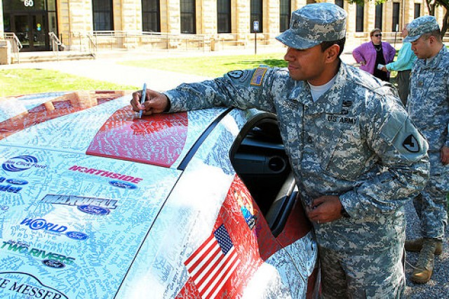 "Staff Sgt. Tom Green, Army Contracting Command-Rock Island, adds his name to the thousands of autographs on the Wounded Warriors Family Support organization's 2014 Ford Mustang GT500 at Rock Island Arsenal, Ill., July 16. The Mustang is being driven to 65 cities in 48 states on a mission to say ""thank you"" and show appreciation to our country's military families for their sacrifices. (Photo by Dawn Marie Barnett, ASC Public Affairs)"