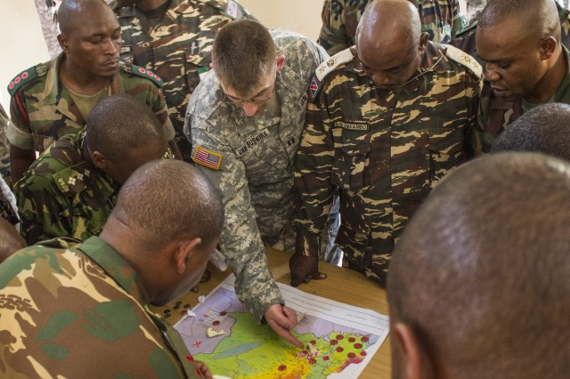 Salima, Malawi—Capt. Joshua Van Buskirk, intelligence officer, New Hampshire Army National Guard (middle), performs mission analysis with a host of partner nation officers during the first week of Southern Accord 14, July 18. SA 14 promotes regional relationships, increases capacity, trains US and Southern African forces, and furthers cross training and interoperability.