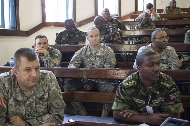 Salima, Malawi—Capt. Paul Wiles, intelligence officer, (bottom left), Capt. Steve Dray (middle), legal officer and Maj. James Crump (back left), intelligence officer, of the 4th Infantry Brigade Combat Team, 1st Infantry Division attend a mission analysis briefing along with Capt. Olly Nyirenda, intelligence officer, Umbutfo Swaziland Defense Force (right), during Southern Accord 14, July 18. SA 14 promotes regional relationships, increases capacity, trains US and Southern African forces, and furthers cross training and interoperability.