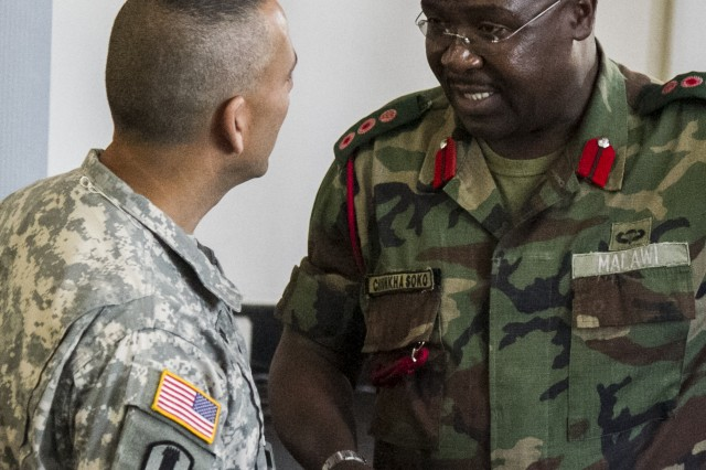Salima, Malawi-- Brig. Gen. Peter L. Corey, deputy-commanding general, U.S. Army Africa, (left) shakes hands with Col. CH. Soko, deputy commandant, Malawi Armed Forces College (right), during the opening ceremony of Southern Accord 14, July 14. Southern Accord is an annual combined, joint exercise that brings together U.S. military personnel with counterparts from various African militaries. The U.S. and other partner nations are working together to ensure they have a common ability to conduct peacekeeping and humanitarian support operations throughout Southern Africa.