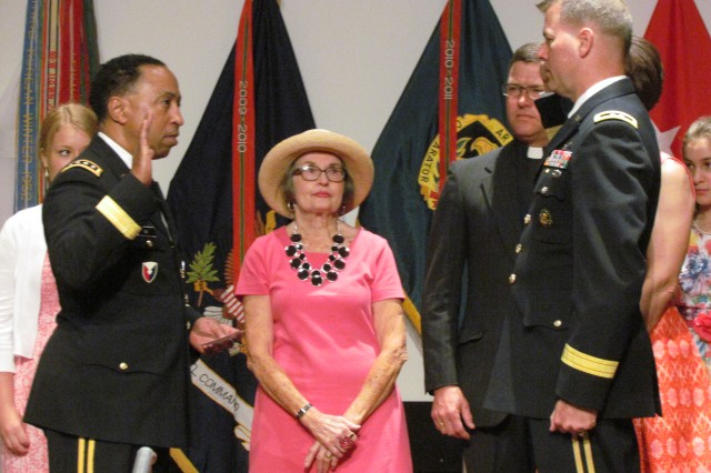Redstone's newest two-star general, Maj. Gen. Ted Harrison, takes the oath of office administered by AMC commander Gen. Dennis Via as his family looks on. Standing between the two officers is Harrison's mother, Julie Harrison.