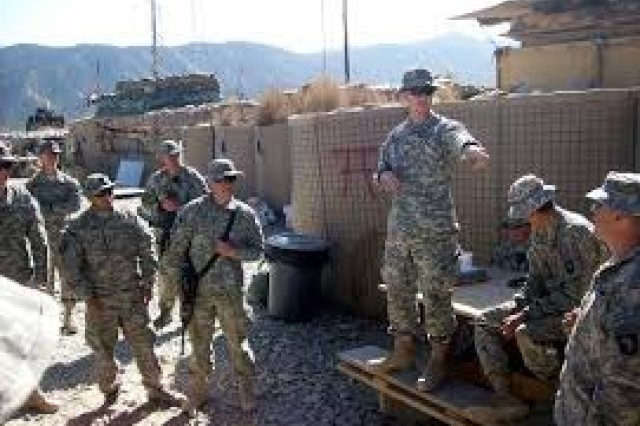 """Chaplain (Capt.) Jared Vineyard, standing on a bench, leads a devotional time with fellow troops in eastern Afghanistan. Vineyard deployed to Afghanistan's dangerous Paktika Province -- known as """"The Badlands"""" -- with the 101st Airborne Division in 2010."""