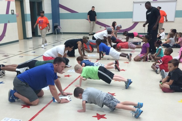 Lt. Col. Scott Ward (left), from Killeen, Texas, and commander of the 479th Field Artillery Brigade's Medical Training Task Force, grades push-ups during a physical fitness test during a YMCA camp at Timber Ridge Elementary School in Killeen, Texas.