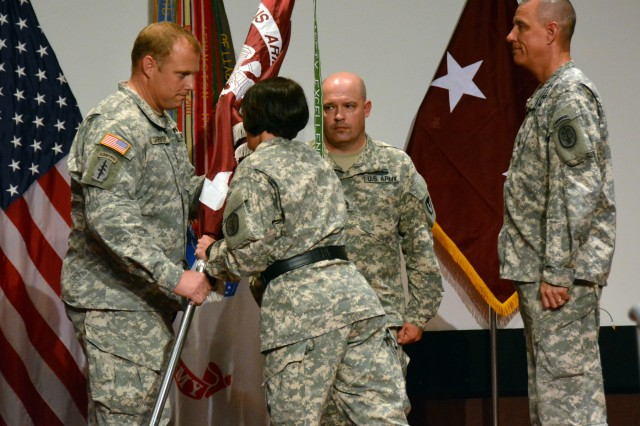 Fox Army Health Center incoming commander Col. David Carpenter accepts the guidon from Maj. Gen. Jimmie Keenan, commander of the Southern Regional Medical Command, during Thursday's change of command. Looking on are outgoing commander Col. William Darby, right, and Sgt. 1st Class William Cooper, center, the noncommissioned officer at Fox.