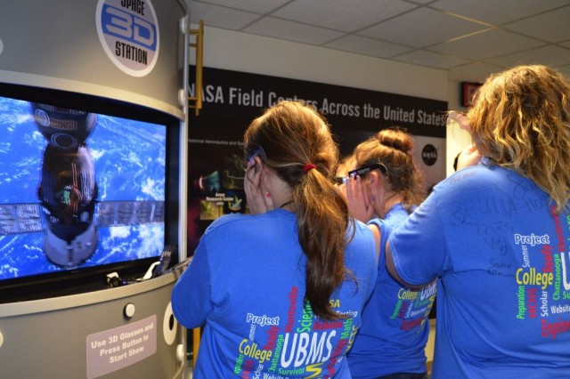 The students watch a movie at Marshall Space Flight Center of 3D footage taken from space.