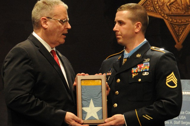 Deputy Defense Secretary Robert Work presents the Medal of Honor flag to Former Staff Sgt. Ryan M. Pitts, Medal of Honor recipient, as Army Secretary John M. McHugh looks on. Pitts was inducted into the Hall of Heroes during a Pentagon ceremony, July 22, 2014.