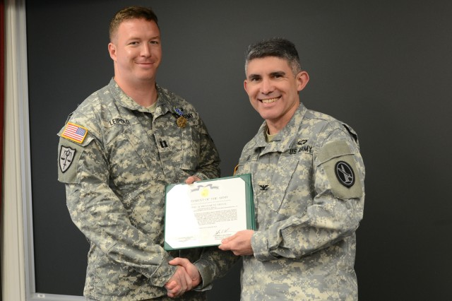 Col. James R. Agar, U.S. Army Military District of Washington's staff judge advocate presents Capt. Calvin A. Leipold III, MDW senior trial counsel the Army Achievement Medal during a ceremony, held at Fort Lesley J. McNair, D.C., July 22, 2014.
