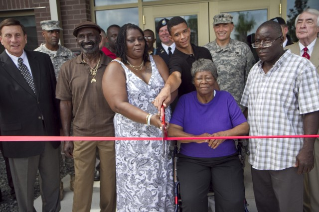 Surrounded by family, friends and supporters, Kasinal Cashe White, holding the scissors, along with her nephew, Andrew Cashe, cut the ribbon to a new Army Reserve facility in Sanford, Fla., on July 19. Kasinal's brother and Andrew's father, Sgt. 1st Class Alwyn Cashe, was honored in a ceremony where the center was renamed in his honor. Cashe, a Silver Star recipient from Oviedo, died Nov. 8, 2005, after heroically rescuing his fellow Soldiers from a burning Bradley Fighting Vehicle the previous October in Diyala, Iraq. Cashe is currently being recommended for the Medal of Honor. Also pictured in front are Congressman John Mica (far left), Ruby Mae Cashe, (seated) mother of the honoree, and Karlos Cashe, (far right) his brother.