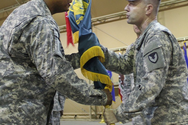 Col. James Kinkade, 402nd Army Field Support Brigade commander, passes the Army Field Support Battalion -- Kuwait colors to the incoming commander, Lt. Col. Earl Schonberg Jr., during a change of command ceremony at Camp Arifjan, Kuwait, July 2. (Photo by Sgt. 1st Class Annette Simon, 402nd AFSB Public Affairs)