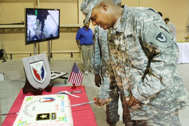 The Army Field Support Battalion -- Kuwait's new commander, Lt. Col. Earl Schonberg Jr., cuts the ceremonial cake during his welcome reception following the change of command ceremony at Camp Arifjan, Kuwait, July 2. (Photo by Sgt. 1st Class Annette Simon, 402nd AFSB Public Affairs)