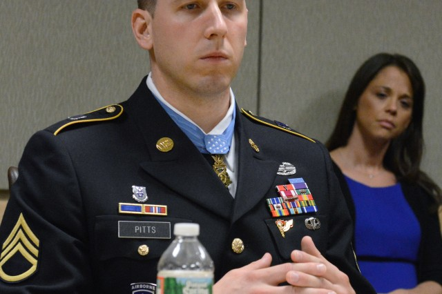 Former Staff Sgt. Ryan M. Pitts speaks about his experiences before, during and after his time in Afghanistan, where his actions of valor earned him the Medal of Honor. Behind him is his wife Amy.