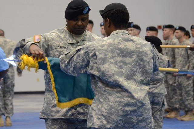Lt. Col. Neil Mahabir, Training Support Battalion commander, and Master Sgt. Jacqueline Hill, acting TSB command sergeant major, case the unit's colors during a ceremony July 22, 2014 at Fort Jackson. S.C.