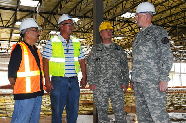 Col. Stuart J. McRae, (far right), Fort Rucker garrison commander, and Command Sgt. Maj. William D. Lohmeyer, (middle right) Fort Rucker garrison command sergeant major, speak with Jess Lira, assistant commissary officer, and Bobby Ward, store director, about how the new commissary construction is going July 21.