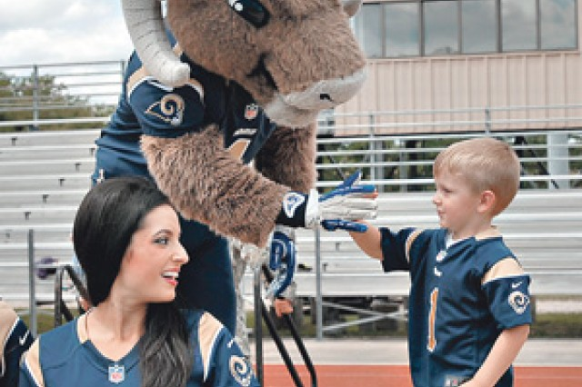 Jackson Burns, 3, gets a high five from the Rams' mascot, Rampage, as Rams cheerleader and U.S. Air Force Capt. Michelle Kolcun, looks during the Rams' NFL Play 60 event held July 16 at Gerlach Field.
