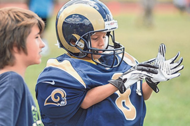 Jayden Burdine, 7, tries on St. Louis quarterback Sam Bradford's helmet, shoulder pads, jersey and gloves as Jayson Manuel, 12, looks on at a station during the NFL Play 60 event held July 16 at Gerlach Field.