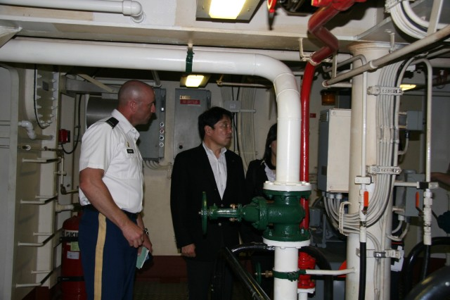 Chief Warrant Officer 4 Rick Deans shows Itsunori Onodra, the Japanese Defense minister, around the U.S. Army Vessel Coamo (LCU-2014), during his visit to Yokohama North Dock, Japan.
