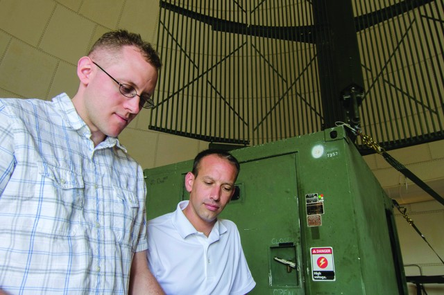 AN/TPS-63 radar technicians Greg Lee, left, and Shawn Kuntz of Tobyhanna Army Depot review final preparations for the Air Traffic Control Radar Beacon System, Identify Friend or Foe, Mark XII/XIIA System testing for the TPS-63 radar. The TPS-63 is a Marine Corps Air Surveillance radar.