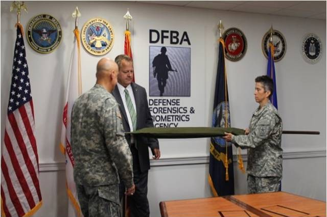 Army Provost Marshal General  Maj. Gen. David Quantock, Donald Salo, director Defense Forensics and Biometrics Agency, and Army Provost Sergeant Major Sgt. Maj. Dawn Rippelmeyer, uncase the DFBA colors, July 23, 2014, in Washington, D.C.