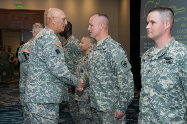 Gen. Ray Odierno, Army chief of staff, congratulates Sgt. 1st Class Kevin Johnson, with the U.S. Army Aviation Center of Excellence, Fort Eustis, Va., on receiving one of the first Army Instructor Badges, during a ceremony July 17, 2014, in Alexandria, Va.