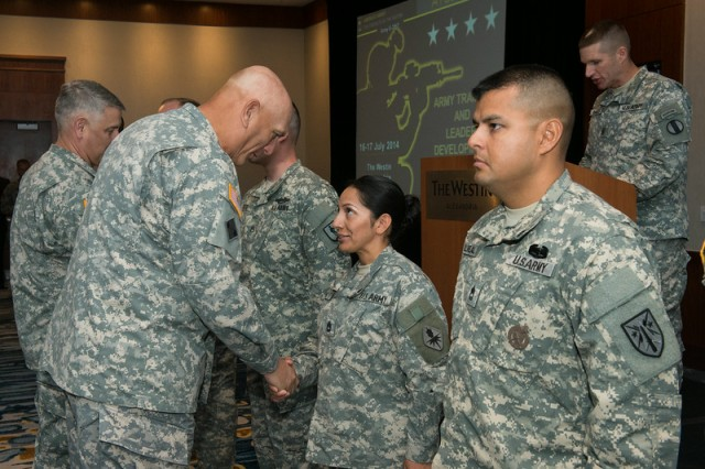 Gen. Ray Odierno, Army chief of staff, congratulates Sgt. 1st Class Jacqueline Sauve, with the U.S. Army Intelligence Center of Excellence, Fort Huachuca, Ariz., on receiving one of the first Army Instructor Badges, during a ceremony July 17, 2014, in Alexandria, Va.