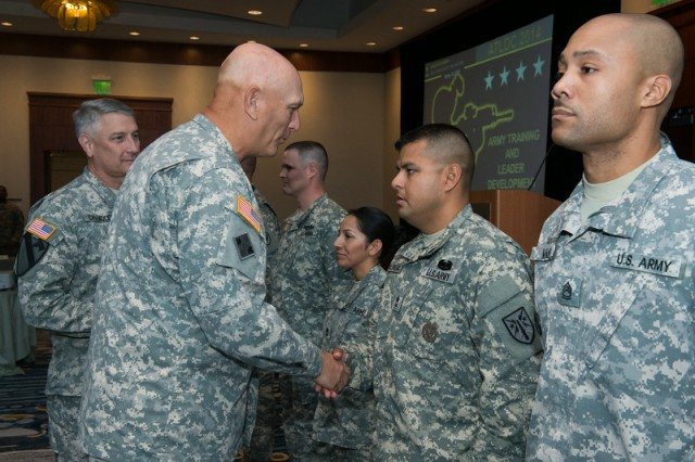 Gen. Ray Odierno, Army chief of staff, congratulates Sgt. 1st Class Adrian Villareal, with the U.S. Army Fires Center of Excellence, Fort Sill, Okla., on receiving one of the first Army Instructor Badges, during a ceremony July 17, 2014, in Alexandria, Va.