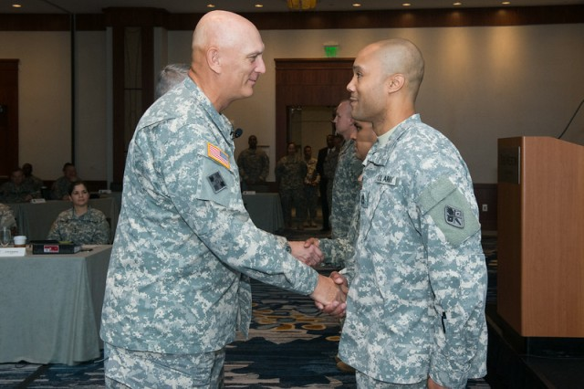 Gen. Ray Odierno, Army chief of staff, congratulates Sgt. 1st Class Bryan Vann, with U.S. Army Cyber Center of Excellence Fort Gordon, Ga., on receiving one of the first Army Instructor Badges, during a ceremony July 17, 2014, in Alexandria, Va.
