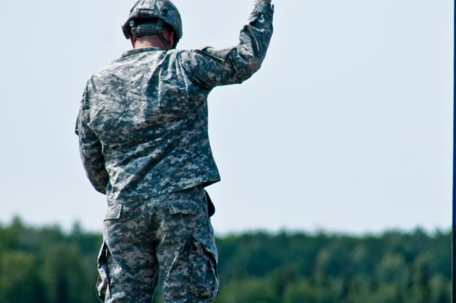 A paratrooper with the 4th Infantry Brigade Combat Team (Airborne), 25th Infantry Division, checks wind conditions shortly before a jump at Malemute Drop Zone on Joint Base Elmendorf-Richardson, Alaska, July 21, 2014. More than 400 paratroopers and equipment will fill the skies each day over Malemute through Wednesday as part of a partnership training event with members of the U.S. Air Force from Joint Base Lewis-McChord, Wash. and Joint Base Pearl Harbor-Hickam, Hawaii. (Photo by U.S. Army Sgt. Eric-James Estrada/Released)