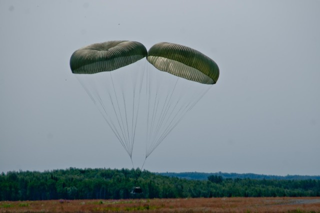 Heavy equipment is dropped from a U.S. Air Force C-17 Globemaster onto Malemute Drop Zone before paratroopers with the 4th Infantry Brigade Combat Team (Airborne), 25th Infantry Division conduct a training parachute assault on Joint Base Elmendorf-Richardson, Alaska, July 21, 2014. More than 400 paratroopers and equipment will fill the skies each day over Malemute through Wednesday as part of a partnership training event with members of the U.S. Air Force from Joint Base Lewis-McChord, Wash. and Joint Base Pearl Harbor-Hickam, Hawaii. (Photo by U.S. Army Sgt. Eric-James Estrada/Released)