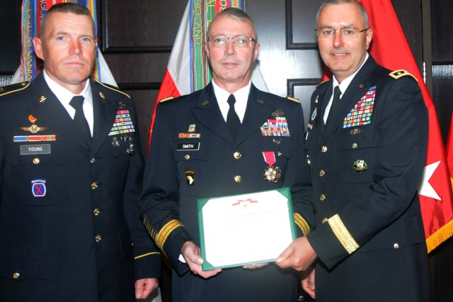 Maj. Gen. Michael Smith (center) First Army deputy commanding general for support, receives the Legion of Merit from First Army Commanding General, Lt. Gen. Michael S. Tucker, during Smith's farewell ceremony in First Army headquarters on Friday. Smith has served as First Army's deputy commanding general for support for 23 months. At left is First Army Command Sgt. Maj. Sam Young.