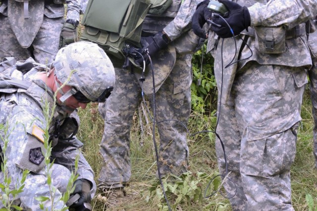 Spc. Philip Brunet of Valley View, Texas, kneels to power up a munitions control unit, while Spc. Jacob Aveila of San Antonio, logs the position in a radio control unit, and Pvt. James Spishak of Los Angeles holds a Defense Advanced GPS Receiver as combat engineers with the 3rd Brigade Engineer Battalion, 3rd Brigade Combat Team, 1st Cavalry Division work together during training on the M7 Spider networked mine system on Fort Hood, Texas. The system allows operators to choose between discharging lethal or non-lethal munitions. (U.S. Army photo by Staff Sgt. Chuck Burden, 3rd BCT PAO, 1st Cavalry Division)