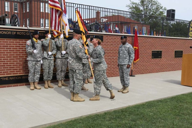 Brig. Gen. Peggy Combs (center), commander, U.S. Army Cadet Command and Fort Knox, Kentucky, passes the command colors to Command Sgt. Maj. Gabriel Arnold (left), incoming senior enlisted leader, as Command Sgt. Maj. Roger Howard right), outgoing senior enlisted leader, looks on, during a change of responsibility ceremony at Cadet Park, Fort Knox, Kentucky, July 25, 2014.