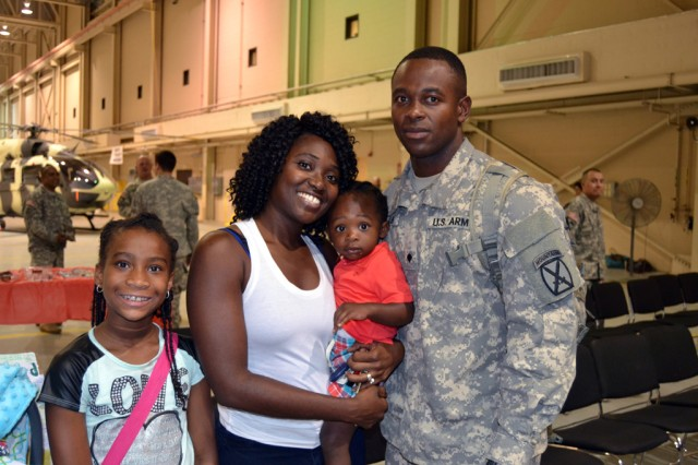 """FORT POLK, La. -- U.S. Army Spc. Kevin Miller (right) with Troop A, 3rd Squadron, 89th Cavalry Regiment stands with his wife, Shaderrica and their children after the troop's homecoming ceremony in the 5th Aviation Battalion hanger July 25, 2014. Troop A returned from a nine month deployment to Cuba. """"It means that my other half is back,  he's been gone 275 days, for a while I didn't think I could do without him, but I managed, but now that he's back it will be even better,"""" said Mrs. Miller. 3rd Squadron is part of 4th Brigade Combat Team, 10th Mountain Division. (U.S. Army photo by: Sgt. 1st Class E. L. Craig, 4th BCT, 10th MTN DIV Public Affairs)"""