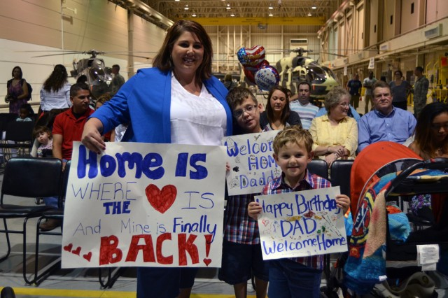 """FORT POLK, La. -- Jackie McCarrick waits with her kids, before the Troop A, 3rd Squadron, 89th Cavalry Regiment's homecoming ceremony in 5th Aviation Battalion's hanger, July 25, 2014, for her husband U.S. Army Sgt. Brandon McCarrick to return. Troop A returned from a nine month deployment to Cuba. """"I get my best friend back,"""" said Mrs. McCarrick. """"The hardest part was my sons crying for their dad, I stayed strong by having a good support system."""" 3rd Squadron is part of 4th Brigade Combat Team, 10th Mountain Division. (U.S. Army photo by: Sgt. 1st Class E. L. Craig, 4th BCT, 10th MTN DIV Public Affairs)"""