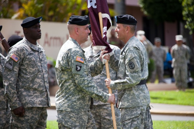 Brig. Gen. Dennis Doyle (right), Commanding General of Pacific Regional Medical Command (PRMC) and outgoing Tripler Army Medical Center (TAMC) Commander, passes the colors to Col. David Dunning (left), incoming TAMC Commander during the Change of Command and Change of Responsibility ceremony July 25, 2014 at 10 a.m. at the TAMC Flag Pole in Honolulu, Hawaii.