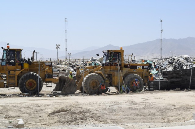 Afghan workers use front-end loaders to sort trash outside the new Waste Management Complex on Bagram Air Field, Afghanistan, July 16, 2014. The trash is sorted for recycling and to ensure that only safely combustible material is introduced to the incinerators. (DoD photo by U.S. Army Maj. Devon McRainey/Released)