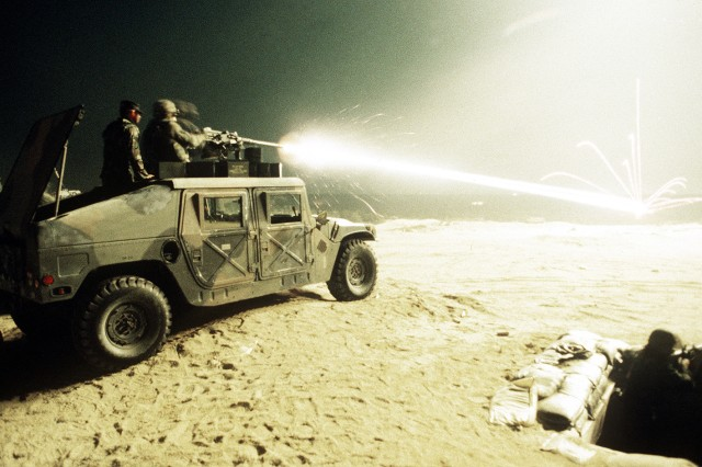 Tracer rounds ricochet off of a tank as security police  fire a  mounted .50-caliber machine gun.