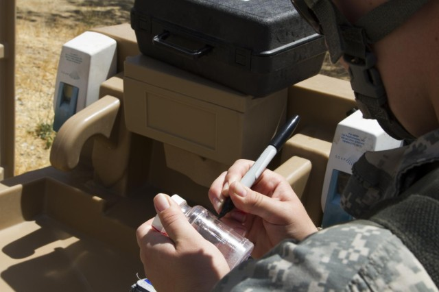 Spc. Brittany J. Dorrill from the 988th Medical Detachment from Round Rock, Texas, labels a water sample from a hand washing station at Forward Operating Base 8J on Fort Hunter Liggett, Calif., during Warrior Exercise (WAREX) 91 14-03. Dorrill takes samples for testing to ensure that Soldiers are not put at risk from water-borne disease. (U.S. Army Reserve photo by Pvt. Travis J. Terreo, 205th Press Camp Headquarters)