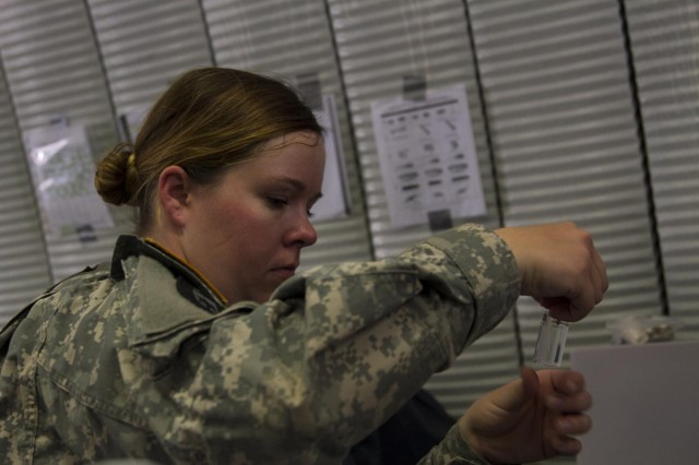 Spc. Brittany J. Dorrill from the 988th Medical Detachment from Round Rock, Texas, prepares a water sample before placing it in an incubator July 24, 2014, during Warrior Exercise (WAREX) 91 14-03 at Fort Hunter Liggett, Calif. Soldiers from preventive medicine take water from drinking fountains, water buffaloes and dining facilities and test them for harmful bacterias. (U.S. Army Reserve photos by Travis J. Terreo, 205th Press Camp Headquarters)
