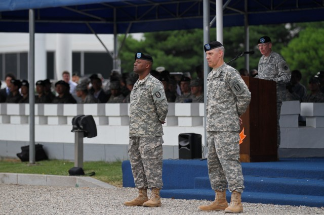 Lt. Gen. Bernard S. Champoux, Commanding General, Eighth Army speaks about Col. Arvesta P. Roberson, incoming 1st Signal Brigade Commander and Col. Paul H. Fredenburgh III, outgoing commander at the Brigade's Change of Command Ceremony at USAG Yongsan's Knight Field July 16, 2014. Champoux said that he expects Roberson to carry on the hard work that Fredenburgh did for the last two years. (U.S. Army Photo by Cpt. Traun C. Moore)