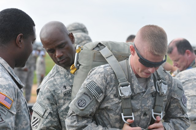 Maj. Eugene K. Mack, chaplain for the 1st Brigade Combat Team, 82nd Airborne Division, helps Sgt. Brian P. Hamilton, chaplain assistant non-commissioned officer in charge for 1st BCT, don a T-11 parachute, July 24, 2014, at Sicily Drop Zone on Fort Bragg, N.C. Mack and Hamilton donned parachutes during an event hosted by the U.S. Army Special Operations Command commemorating the 239th anniversary of the Chaplain Corps.