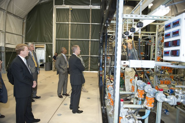 Edgewood Chemical Biological Center chemical engineer Adam Baker (right) explains the Field Deployable Hydrolysis System to Under Secretary of the Army Brad Carson (center) at Aberdeen Proving Ground, Md., July 29, 2014.