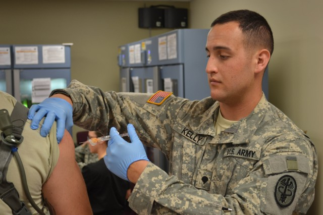 Spc. Jeremy Kelly, medic for 30th Adjutant General Reception Battalion, adminsters medication via injection to an initial entry Soldier.