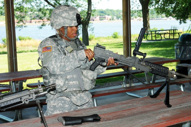 "Spc. Marsha Diana Feightner disassembles the M240B machine gun during the Army Materiel Command's ""Best Warrior"" competition at Rock Island Arsenal, Ill., July 28. Competitors were evaluated on their weapons knowledge by disassembling, assembling and performing function checks on four weapons. (Photo by Tony Lopez, JMC Public Affairs)"