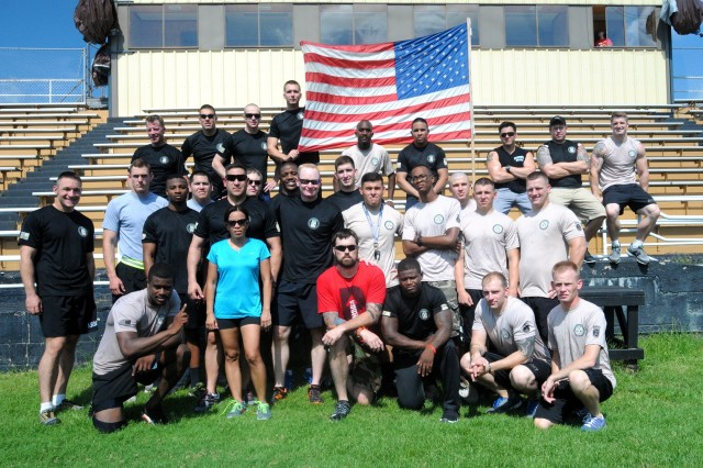FORT POLK, La. -- 2nd Battalion, 4th Infantry, 4th Brigade Combat Team, 10th Mountain Division team possess for a picture after winning the team competition at the Push Up for Charity event at Leesville High School's Wampus Cat Stadium on July 26, 2014. The Warrior Battalion team successfully completed 6,956 pushups raising $420 for the Boot Campaign that helps wounded warriors around the country. (Photo by Sgt. David Edge; 4th BCT, 10th MTN DIV Public Affairs)