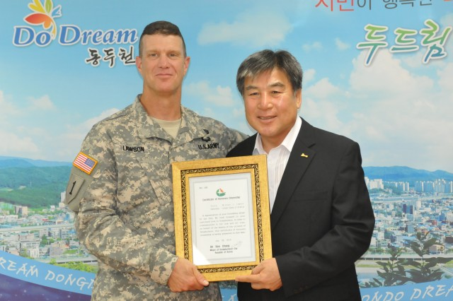 "CAMP CASEY, South Korea -- Col. Michael Lawson, the commander of 210th Field Artillery Brigade, 2nd Infantry Division, poses for a picture with Mayor Oh Se-chang, the mayor of Dongducheon, after becoming an honorary citizen of Dongducheon, South Korea, July 28, 2014 at Dongducheon City Hall.  Mayor Oh thanked them for their service and their hard work to strengthen the relationship with local communities. ""I would like to thank Col. Lawson and Command Sgt. Maj. Brinton for helping out within local communities such as the English Village program,"" said Oh. ""I would also like to have these relationships continue between Soldiers and the city of Dongducheon."""