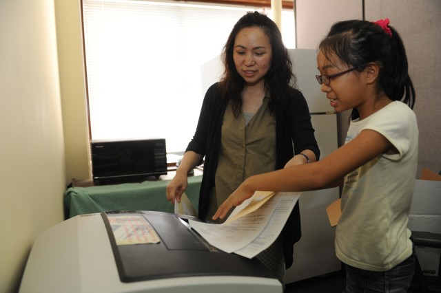 "Ryuko Izumi shows her daughter, Himawari Izumi, how to use a copy machine during the third annual ""Bring Your Kids to Work Day"" event held July 25 on the Camp Zama installation. (U.S. Army photo by Noriko Kudo)"