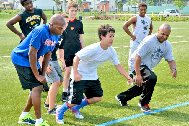 Coach Reginald Thomas (left) and Coach Curtis Hopkins encourage Brendan Mason to give it his all during a sprint exercise at Football Camp.