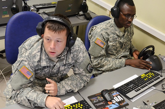 Sgt. Jessie Lingerfelt (left) and Spc. David Adebesin, Charlie Detachment, 106th Financial Management Support Unit, take part in the first ever, networked Europe-wide unit training with sister detachment and headquarters in Germany July 17. More than 20 detachment Soldiers participated in the Virtual Battle Space 2 based deployment exercise from the Mission Training Center on Caserma Ederle, while other components joined the exercise from Baumholder, Kaiserslautern and Grafenwoehr, Germany.